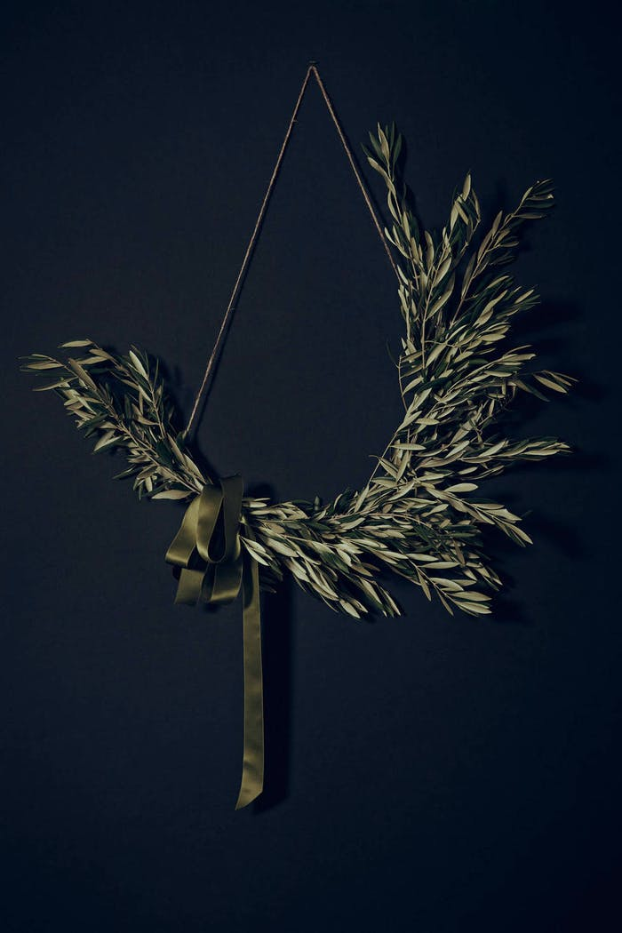 """Olive twigs asymmetric wreath on a dark blue background.<span class=""""sr-only""""> (opened in a new window/tab)</span>"""