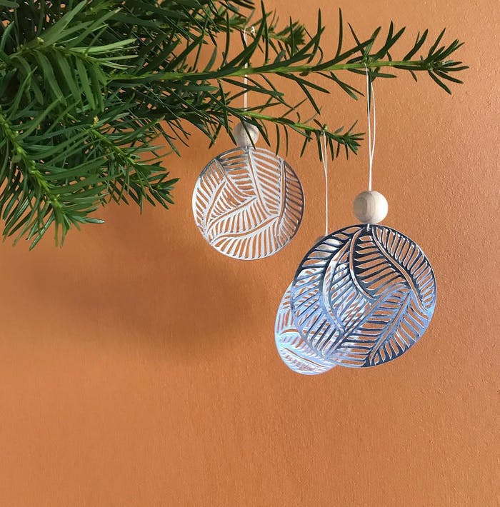 """Paper cut ornament made with a silver foiled paper.<span class=""""sr-only""""> (opened in a new window/tab)</span>"""
