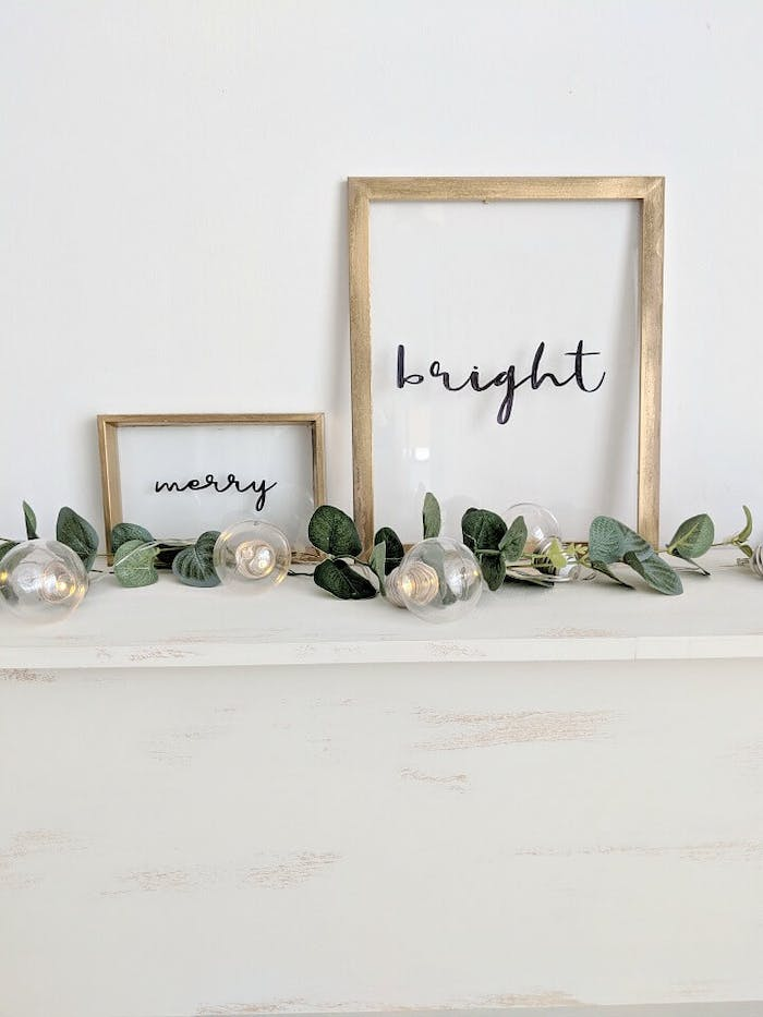 """""""Merry"""" and """"Bright"""" words written into the glass on a picture frame.<span class=""""sr-only""""> (opened in a new window/tab)</span>"""