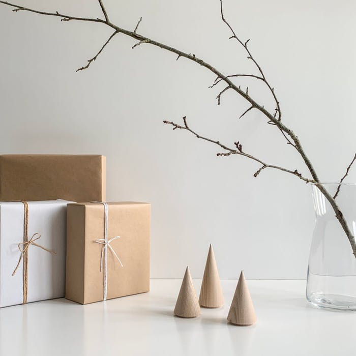 """Wooden minimal trees on a table with gifts next to them.<span class=""""sr-only""""> (opened in a new window/tab)</span>"""