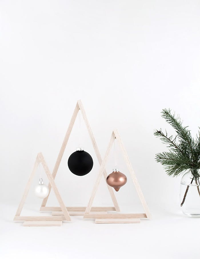 """Wood triangles with a bauble hanging in the middle are a minimal interpretation of a Christmas tree.<span class=""""sr-only""""> (opened in a new window/tab)</span>"""