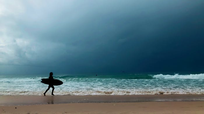 """A surfer on the beach.<span class=""""sr-only""""> (opened in a new window/tab)</span>"""