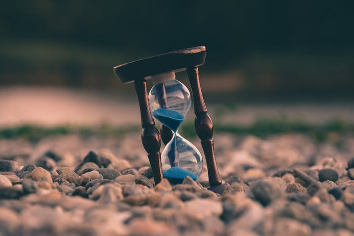 """Hourglass resting on a stone beach.<span class=""""sr-only""""> (opened in a new window/tab)</span>"""