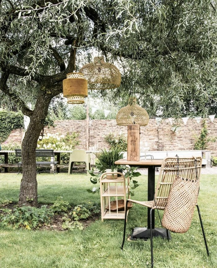 "Rattan pendant lamps and furniture styled in a garden under a big tree.<span class=""sr-only""> (opened in a new window/tab)</span>"