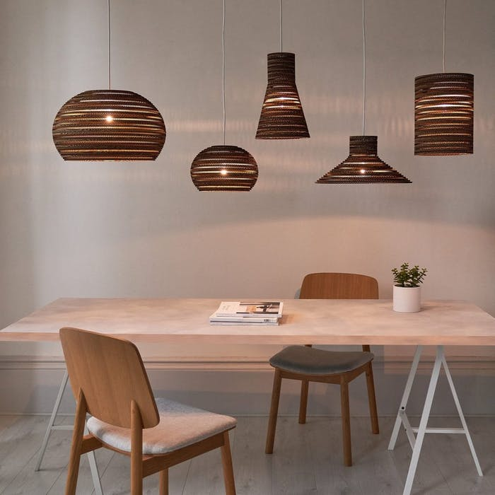 "Pendant lamps made of corrugated cardboard displayed over a table.<span class=""sr-only""> (opened in a new window/tab)</span>"