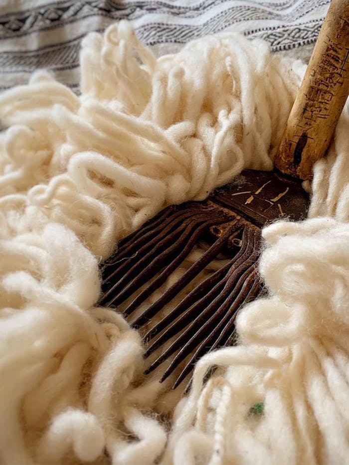 """Close-up of wool fibre and a tool to manually pamper it.<span class=""""sr-only""""> (opened in a new window/tab)</span>"""