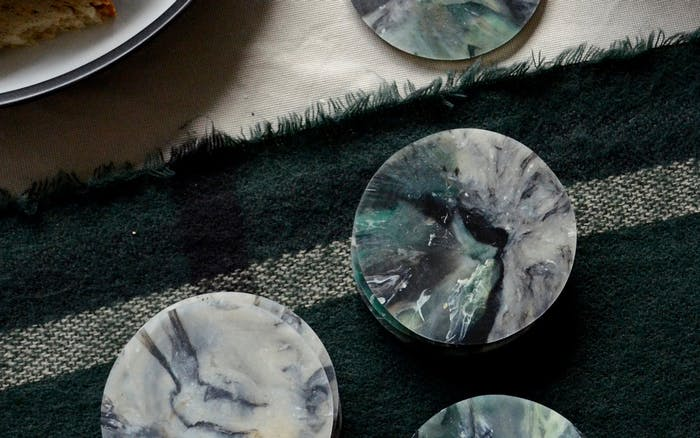 "Top view of a table with marbled sustainable coasters made of recycled plastic.<span class=""sr-only""> (opened in a new window/tab)</span>"