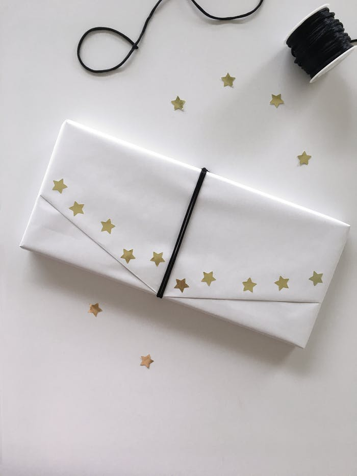 "Gift wrapped in ordinary white paper and decorated with a ribbon and golden paper stars as an example of sustainable gift wrapping.<span class=""sr-only""> (opened in a new window/tab)</span>"