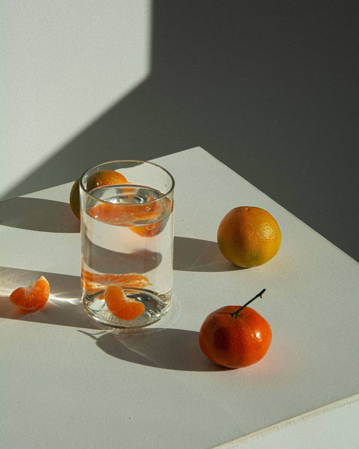 """Close-up of the glass styled with mandarins on a white table.<span class=""""sr-only""""> (opened in a new window/tab)</span>"""