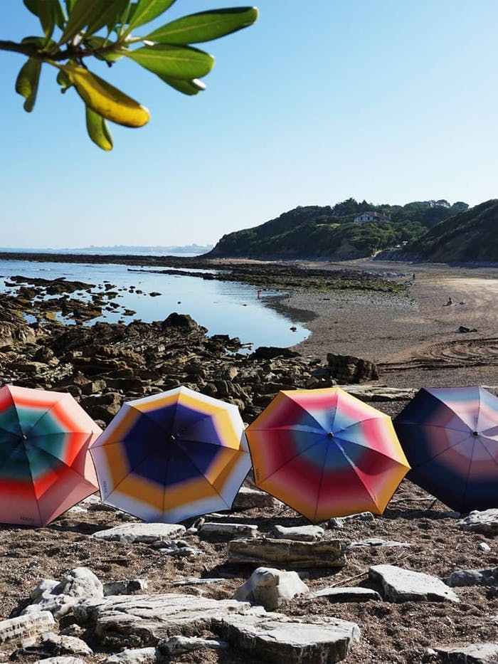 """Sun umbrellas line up on a rocky beach.<span class=""""sr-only""""> (opened in a new window/tab)</span>"""