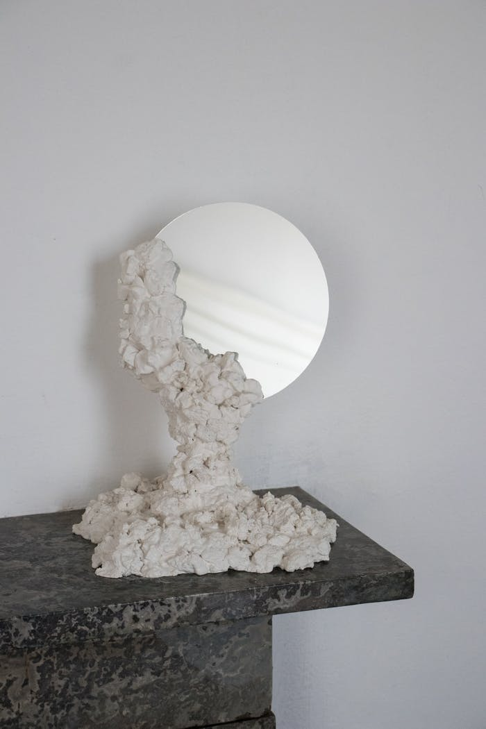 "Round mirror kept in place with a recycled stone base.<span class=""sr-only""> (opened in a new window/tab)</span>"