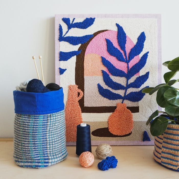 """Textile artwork leaning on a wall and styled with a plant.<span class=""""sr-only""""> (opened in a new window/tab)</span>"""