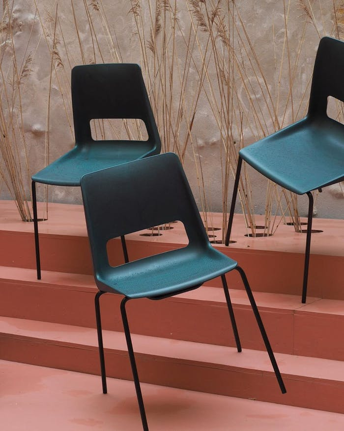 """Upcycled plastic chairs displayed against foliage.<span class=""""sr-only""""> (opened in a new window/tab)</span>"""