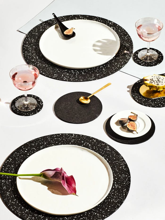 """Table set with black recycled rubber placemats.<span class=""""sr-only""""> (opened in a new window/tab)</span>"""