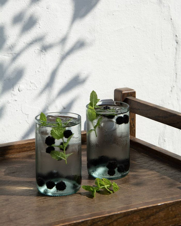 """Recycled glass water glasses styled on a bar cart.<span class=""""sr-only""""> (opened in a new window/tab)</span>"""