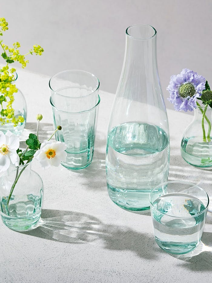 """Recycled glass carafe and glasses styled on a table with flowers.<span class=""""sr-only""""> (opened in a new window/tab)</span>"""