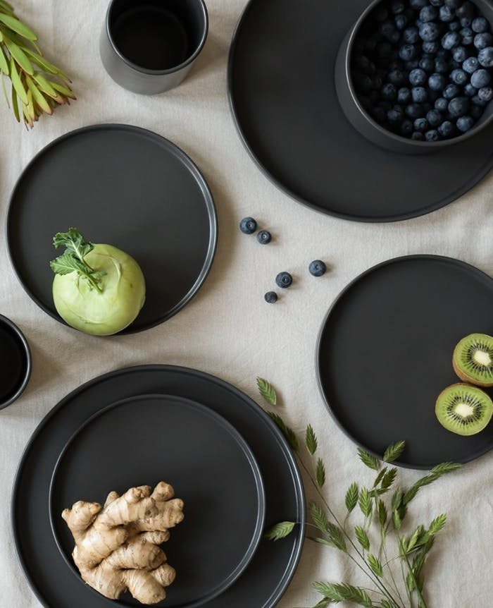 """Flatlay of black plates with green food.<span class=""""sr-only""""> (opened in a new window/tab)</span>"""