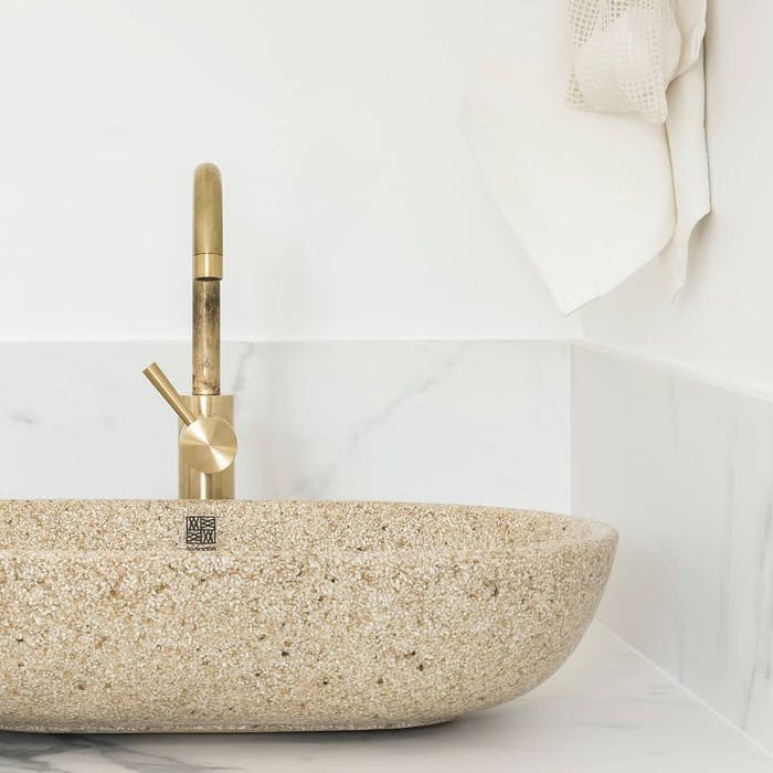"""Sustainable design basin in natural wood colour with brass faucet mounted over a white top.<span class=""""sr-only""""> (opened in a new window/tab)</span>"""