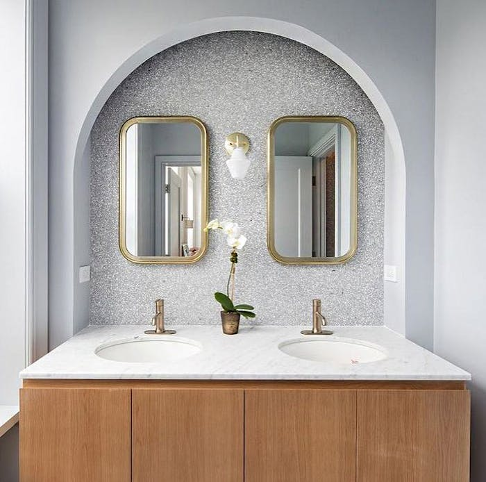 """Bathroom vanity with back wall covered with sustainable terrazzo tiles in grey.<span class=""""sr-only""""> (opened in a new window/tab)</span>"""